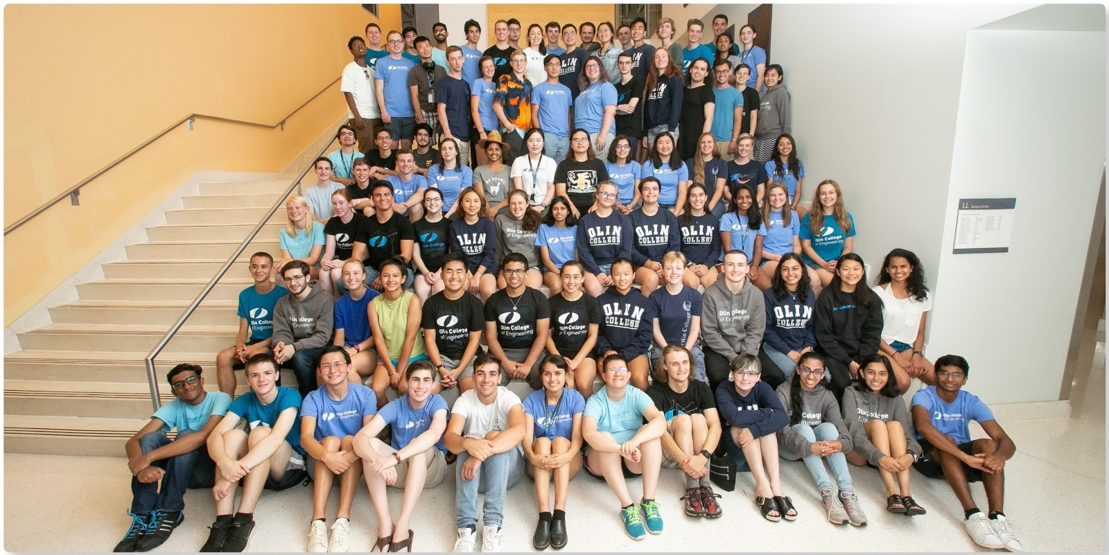 A group picture of a bunch of students, many of whom are wearing Olin shirts.