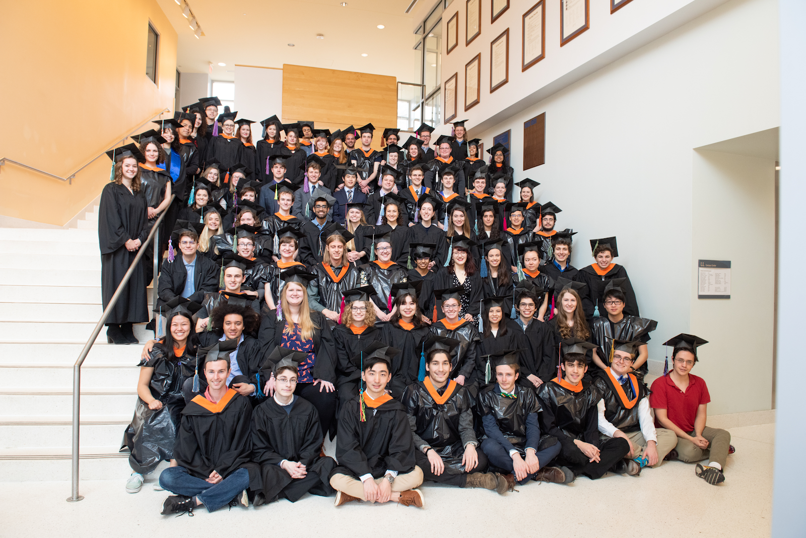 A group photo of people wearing graduation caps and gowns, some of which appear to be homemade.
