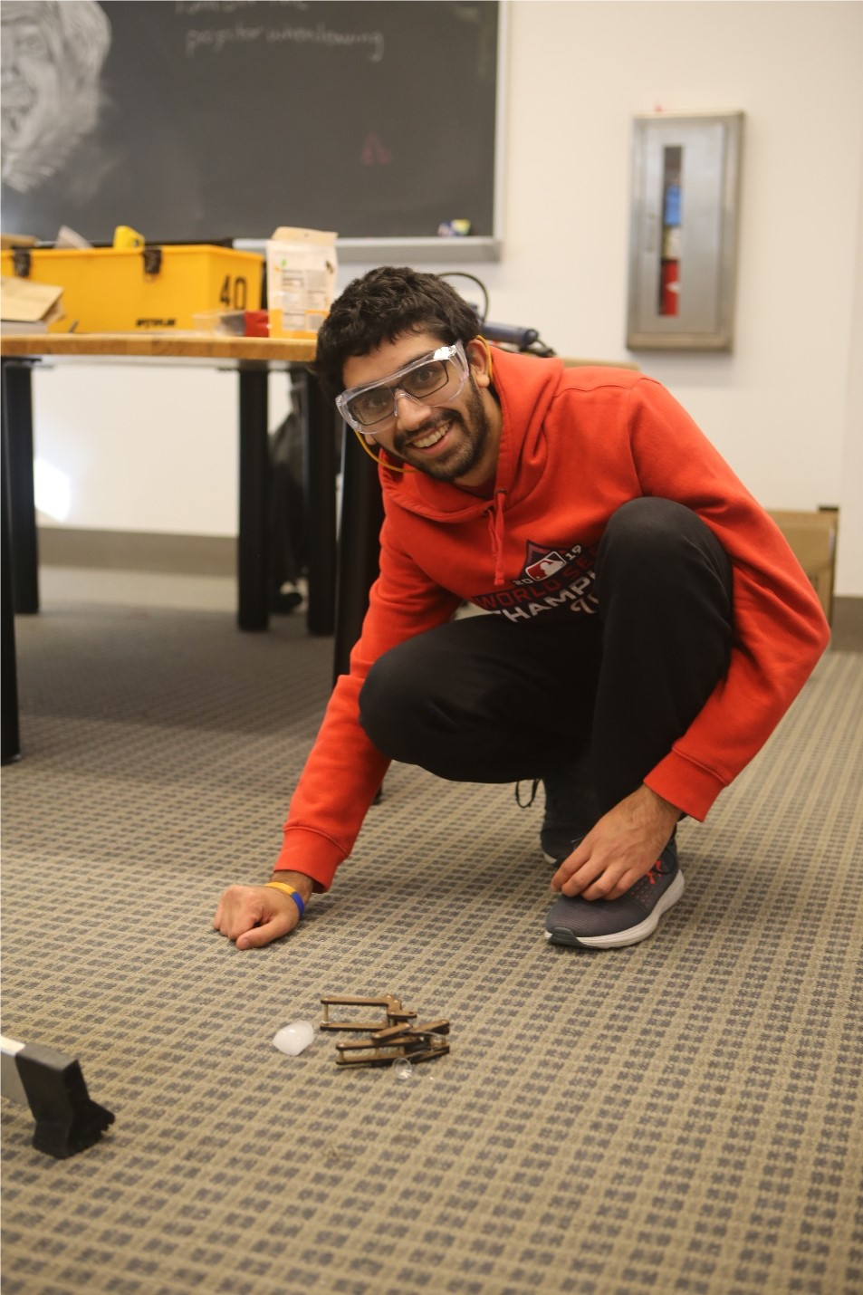 A student wearing safety glasses crouching on the floor with an engineering project.
