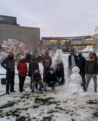 A group of students outside in the snow next to a snowman and igloo.