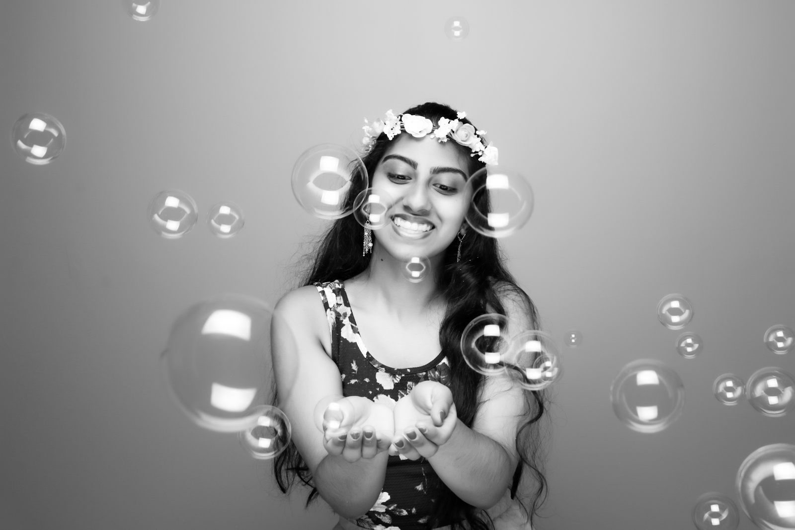 A black-and-white photo of the author with a flower crown and bubbles.