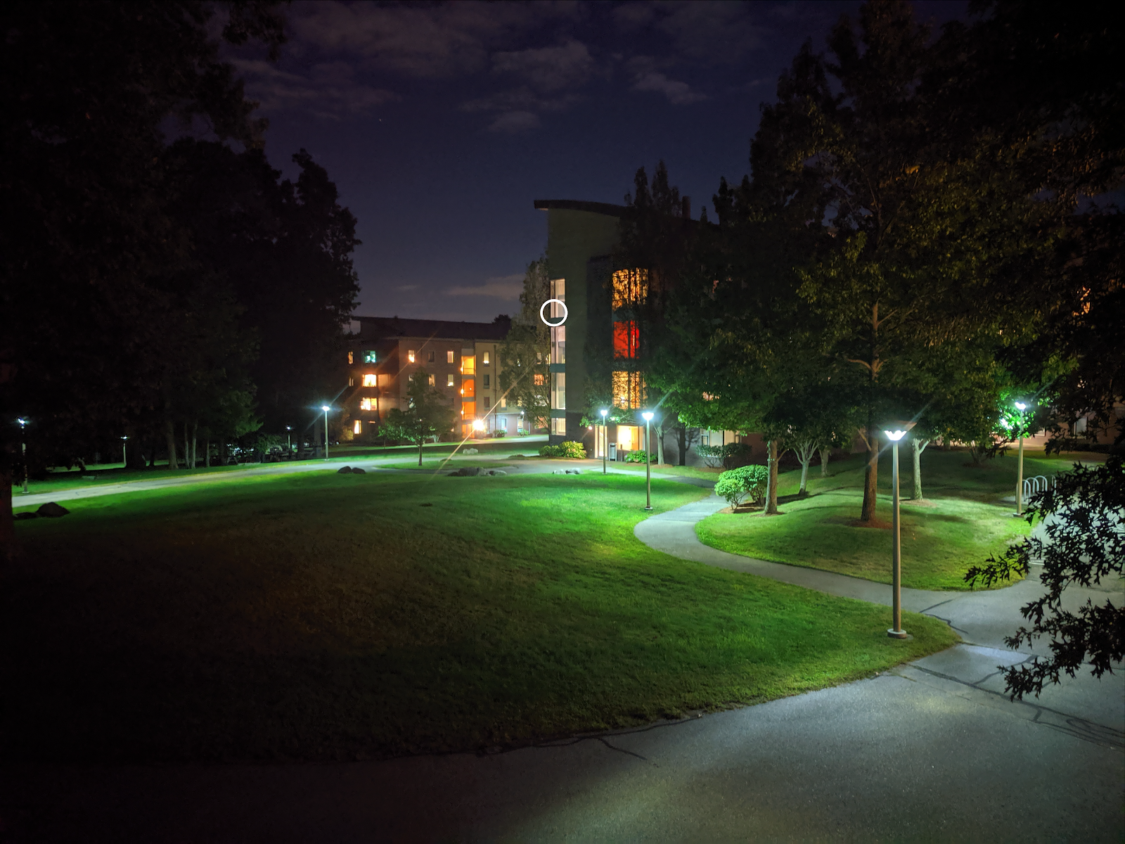 The outside of Olin's West Hall residence hall at night, with a stairwell on the fourth floor circled for emphasis.