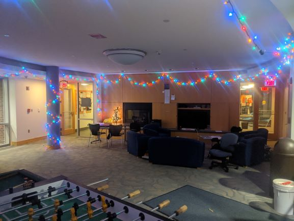 The West Hall 1 lounge with seating, string lights, and a foosball table.